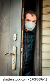 A man in a medical mask on the threshold of his house. Coronavirus Quarantine Isolation