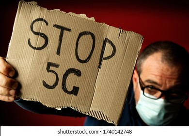 A man in a medical mask shows a Stop 5G poster. Coronavirus Fake News Concept