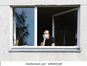 Man in medical protective face mask looking through window.Coronavirus pandemic covid-19.Man in corona quarantine looking out of window to the street.Man with face mask at home.During covid-19 quarant - Shutterstock ID 1696401328