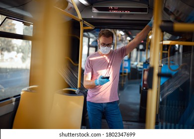 Man with medical protective mask and gloves standing in an emtpy bus.