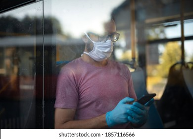 Man with medical protective mask and gloves sitting in an emtpy bus.