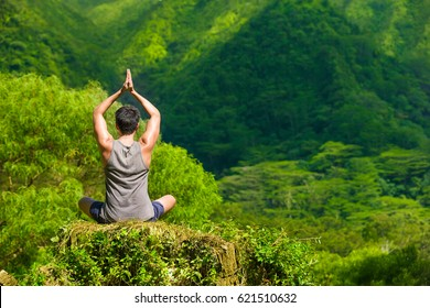 Man meditating in a beautiful mountain setting.