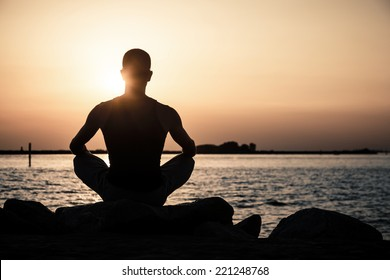 Man meditating on the beach at sunset.