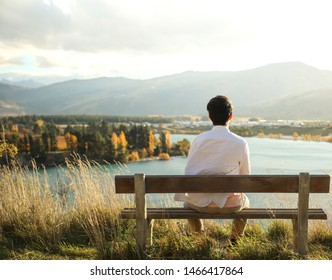 A  man is meditating on dry leaf in the park with face raised up to sky and eyes closed on sunny autumn season. Concept of meditation, dreaming, well-being and healthy lifestyle-Man.