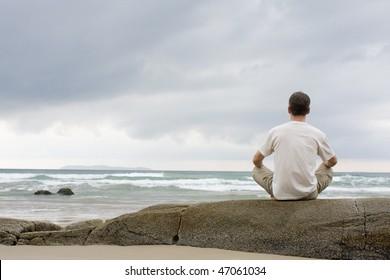 Man meditating on a rock at the sea