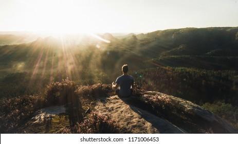 Man meditating in on rocky cliff. Sportsman practicing Yoga on stone edge above landscape, Europe (Saechsische Schweiz)