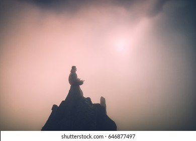 Man meditating in sitting yoga position on the top of a mountain above clouds at sunset light. Zen, meditation, peace. Instagram stylization.