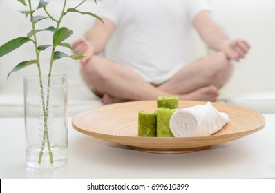Man meditating in Spa with white T-shirt  with candle and towel