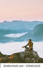 Man meditating in sunset mountains yoga relaxing alone outdoor travel vacations harmony with nature silence