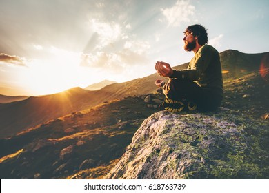 Man meditating yoga lotus pose at sunset mountains Travel Lifestyle relaxation emotional concept summer vacations outdoor harmony with nature