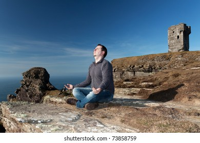 Man at meditation on the Cliffs of Moher - Ireland