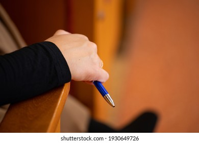 A man at a meeting in a conference room holds a ballpoint pen in his hand. Ballpoint pen large in hand.