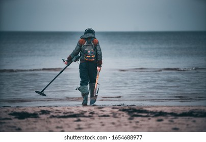 Man with a metal detector on a sea sandy beach.