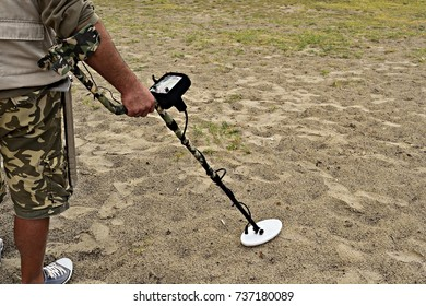man with metal detector in perlustration on a beach