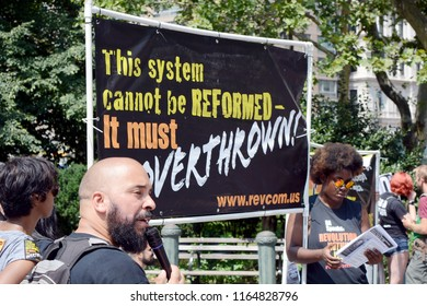 Man With Microphone In Front of Anti Government Sign at Protest of Supreme Court Nominee Brett Kavanaugh In Foley Square, New York, NY, USA - August 26, 2018