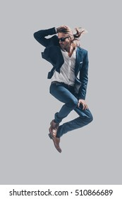Man in mid-air. Handsome young man in full suit and sunglasses jumping against grey background
