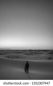 Man in the middle of the Sahara Desert at sunset doing sandboarding in Merzouga, Morocco.