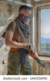 Man in military camo clothes, half face bandit mask and shemagh scarf with machine gun in hands staying inside abandoned building and looking in the broken window. Soldier or sniper or terrorist
