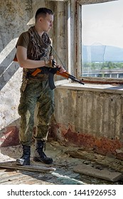 Man in military camo clothes and shemagh scarf with machine gun in hands staying inside abandoned building and looking in the broken window. Soldier or sniper or war criminal or terrorist or assassin