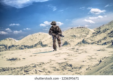 Man in military camouflage uniform with airsoft weapon bending down and running during armed conflict, military battle imitation in sandy or desert area. Airsoft player under fire searching cover