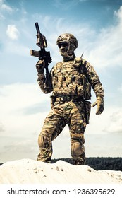 Man in military camouflage uniform and mask, equipped tactical ammunition, standing on sand dune with service rifle replica in hands, cloudy sky on background. Airsoft player taking part in war games