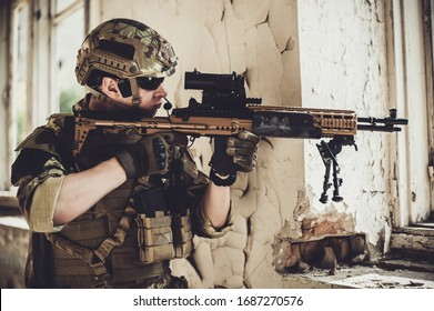 man in military camouflage vegetato uniform with automatic assault rifle with optical sight shoots from the window in the old destroyed building