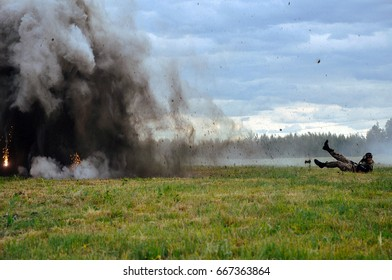 Man in military clothes in a gas mask shoots from a firearm and its covers by the explosion. War. Fight scenes
