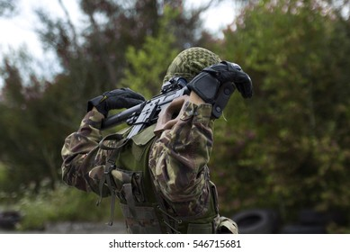 A man in a military form of trying to get out of the hatch. Military on a mission. Game of paintball in a military style.