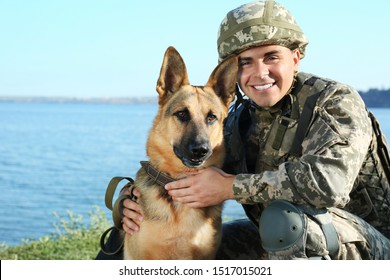Man in military uniform with German shepherd dog near river
