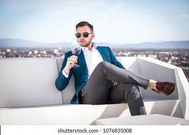 Man millionaire in expensive custom tailored suit, sitting outdoors with glasses and holding a glass of red wine
