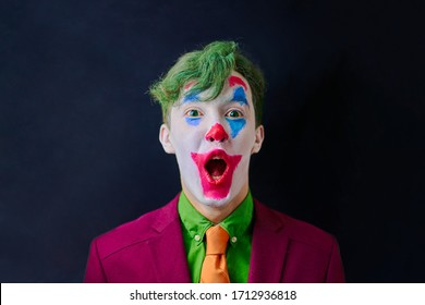 Man in mime makeup cosplay with green hair and a red suit an orange tie and a green shirt. Clown surprised or shocked