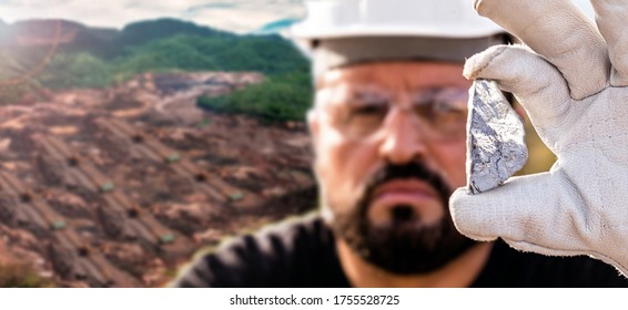 man miner holding silver stone, in the background a large open pit mining company in the city of mexico, Zacatecas.