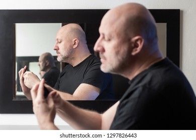 The man at the mirror. A man carefully examines something in his hands. Bald man The man is studying something. Cns.