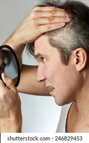 Man with mirror looking at his hair on gray background