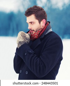 man in mittens freezes and warms his hands outdoors in winter cold day looking away, side view