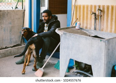 Man mixed race, dark skin, african hair seating near home with black and brown color dog