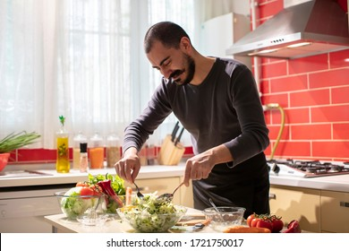 Man Mixing Salad with Lettuce and Parsley in Bowl