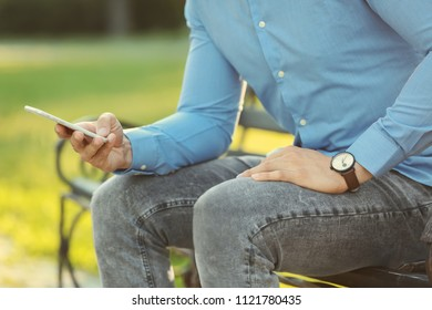 Man with mobile phone resting on bench in park, closeup