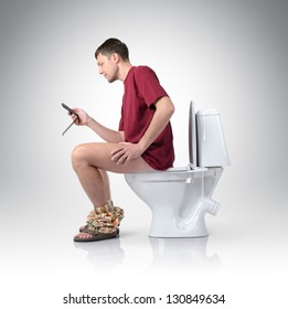 Man with mobile phone sitting on the toilet