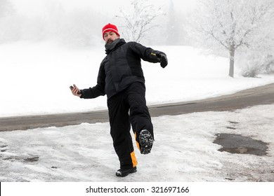 Man with mobile phone is slipping on a freezy way