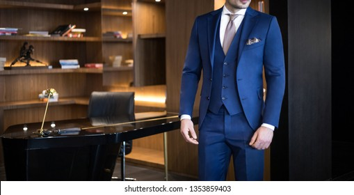 Man model in expensive custom tailored suit standing in his office and posing