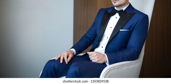 Man model in expensive custom tailored blue tuxedo, suit sitting and posing indoors