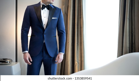 Man model in expensive custom tailored blue tuxedo, suit standing and posing indoors