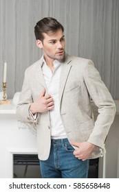 Man model in light beige linen jacket, white shirt and blue jeans near fireplace