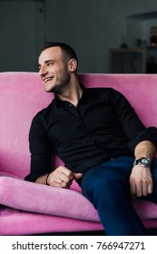 Man model sits on pink sofa in loft interior. Businessman in a black shirt and watch, blue pants. lies on the couch.