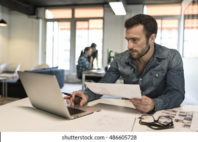 Man in modern office start-up working on laptop. Casual business man using computer