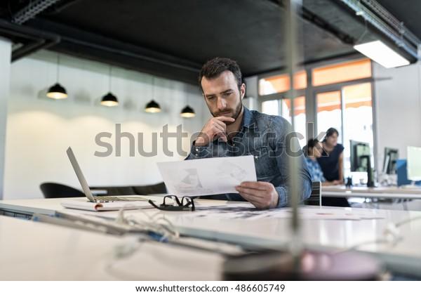 Man in modern office start-up working on laptop.