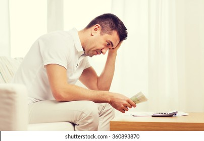 man with money and calculator at home