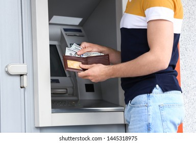 Man with money near cash machine outdoors, closeup