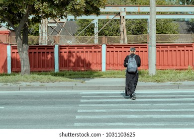 A man in a monk's clothes crosses the road